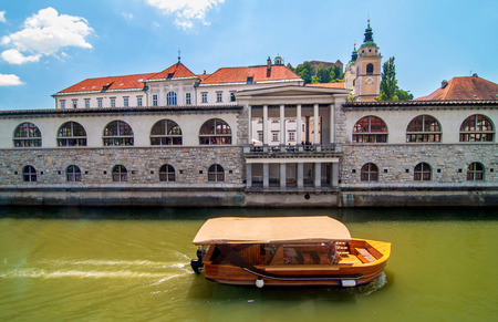 st nicholas: Boat on Ljubljanica river and St. Nicholas church in the background on a bright sunny day, Ljubljana, Slovenia