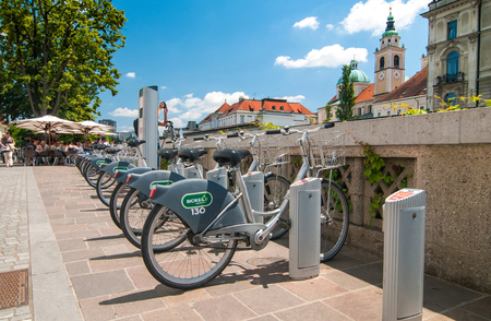 Ljubljana, Slovenia - June 7, 2016 Bicycle sharing system, called Bicikelj and St. Nicholas church in the background on a bright sunny day