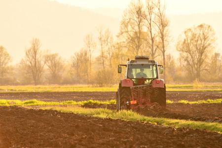 Farmer plowing soil at sunset in spring season