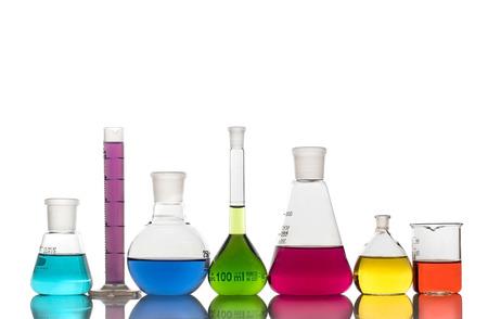 Cristalería de laboratorio con líquidos de colores sobre fondo blanco. Foto de archivo
