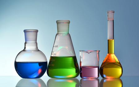 Verrerie de laboratoire avec des liquides colorés et des produits chimiques sur fond bleu