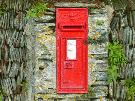 Red postbox on gray wall