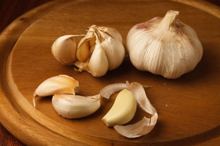 cloves and head garlic on cutting board Stock Photo