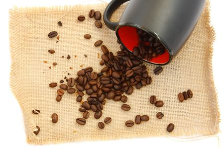 coffee beans spilling from black cup on burlap.white background