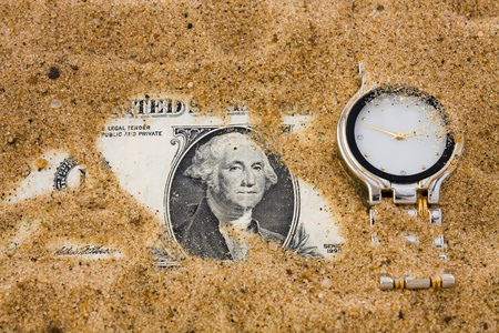 One dollar and watch in sand