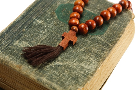 rosary beads on old book. white background Stock Photo