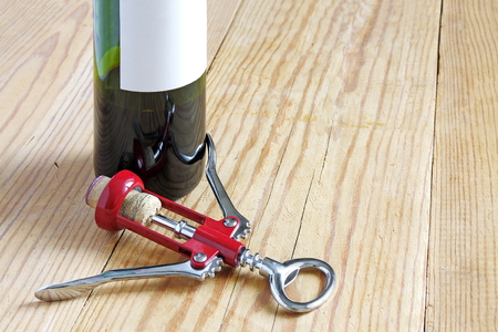 Red  corkscrew  with wine bottle on wooden plate. Close up. Stock Photo