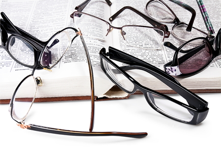 heap eyeglasses  on  book. white background