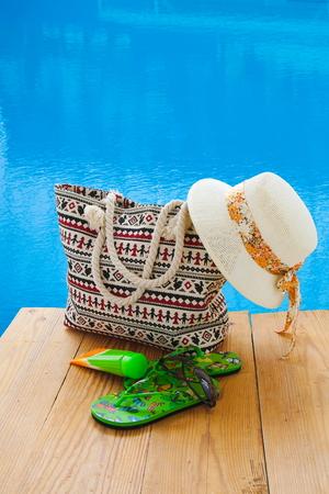 beach accessories on wood near blue water