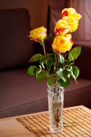 vase with yellow roses on table in room.