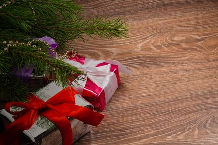 branch fir  and presents with christmas ornament. Wooden background