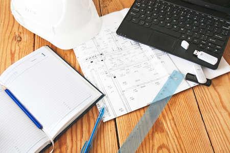 helmet, notebook, drawing tools on wooden plate