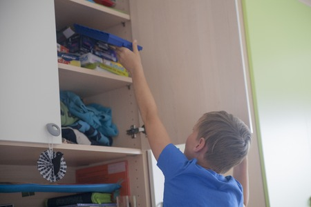 A nine years old boy organizing his messy bedroom Reklamní fotografie