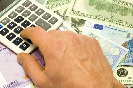 Dollar, euro banknotes, calculator, human hand pushing button photo