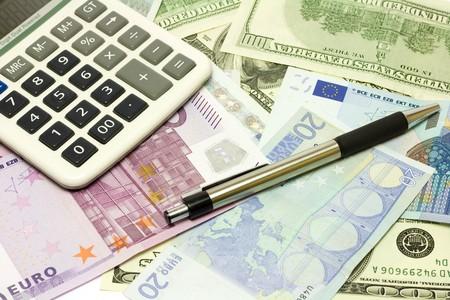 Dollar, euro banknotes, calculator and pen photo