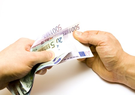 pulling money: One hand holding money, other pulling banknote Stock Photo