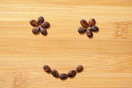 watermelon seeds on wooden background, smiley face 版權商用圖片