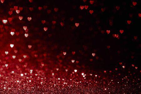 Valentijnsdag achtergrond met rode harten glitter bokeh op zwart, kaart voor Valentijnsdag, Kerstmis en huwelijksfeest, liefde bokeh glanzende confetti getextureerde sjabloon