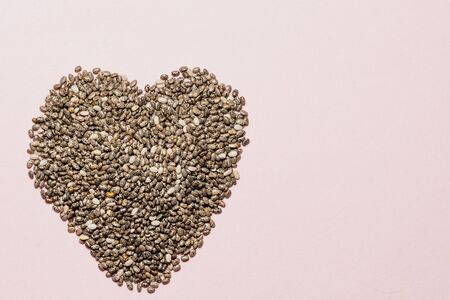 heart made of chia seeds on pink, healthy life and nutrition concept