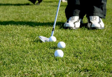 A golf club (driver) about to strike a golf ball on a tee Stock Photo