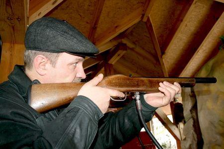 rifleman: A man is shooting  at a shooting range.