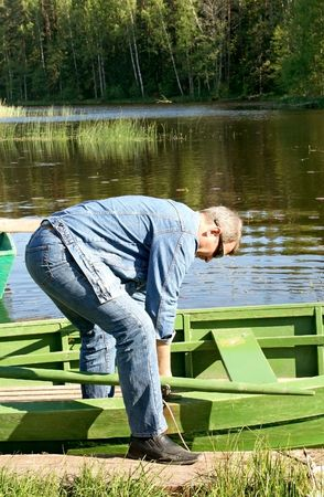 A man unties a boat, what to swim on a lake photo