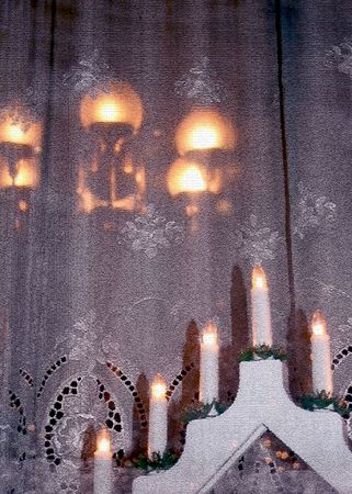 homely: Christmas arrangement of electric candles on a wooden window sill creating warm homely atmosphere
