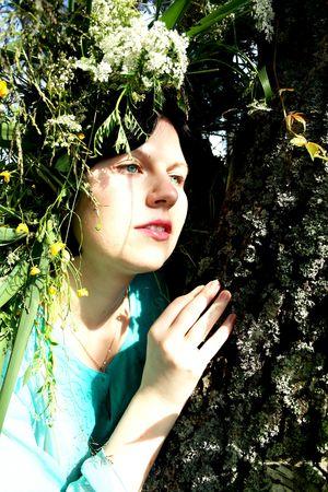 Blue-eyed brunette in chaplet on background bark old tree photo