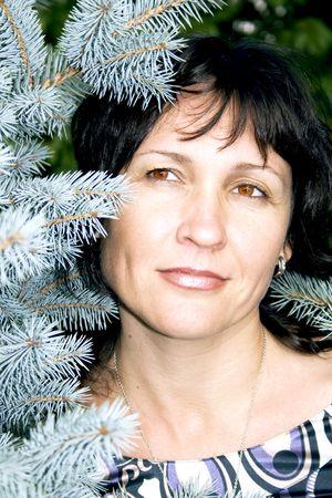 Portrait attractive brunette on a background a blue fir-tree photo