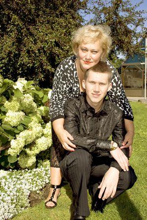A mother in a garden hugs a son, which was eighteen years ago photo