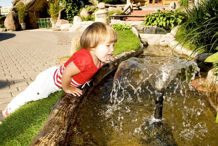 Little and active girl tries to drink from a water fountain photo