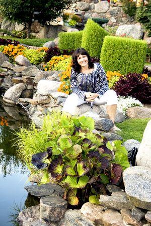 Pretty brunette relaxing in beautiful garden