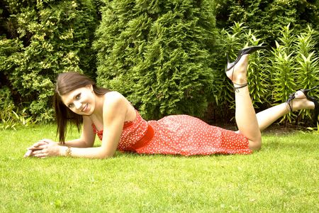 Pretty young smiling lady relaxing in summer garden Stock Photo - 5445984