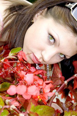 Portrait pretty brunette in surroundings a red begonia closeup photo