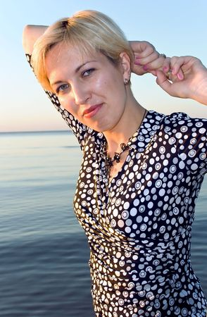 Attractive blonde on a background quiet water of the Baltic sea photo