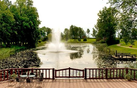 Fountain on the river in an autumn park with a wooden dais