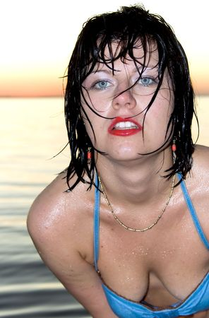 Young brunette after bathing in the Baltic sea on sunset photo
