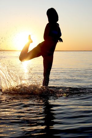 Silhouette of a woman in the sea performing yoga at sunset photo