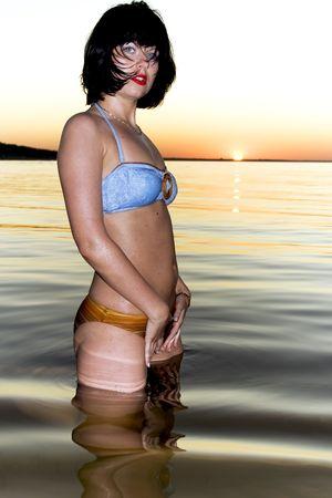 Young blue-eyed brunette on sunset background photo