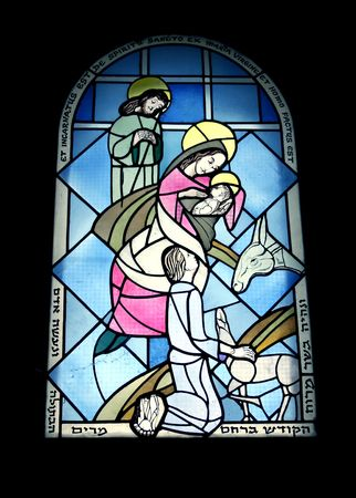 Stained glass window in the monastery of benedictines  19th century of baby Jesus, Mary, and Joseph in the manger with the animals. photo