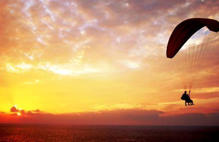 Flight of paroplane above Mediterranean sea on sunset