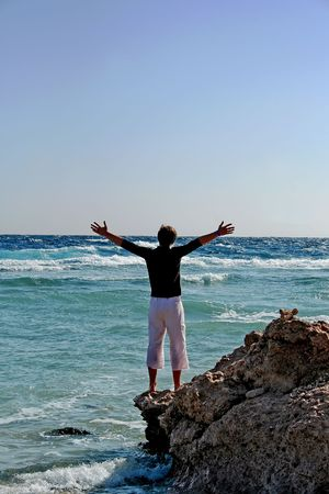 Young man on coast the Red sea, having lifted hands towards to freedom photo