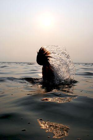 Girl splashing in Baltic sea water at sunset photo