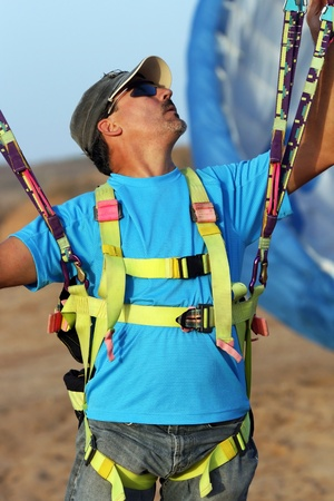 slings: The glider pilot prepares for flight on a paraplane