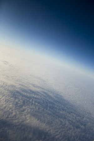 Blue sky and puffy clouds with the brightly expressed atmosphere on height of 5000 m above Earth photo