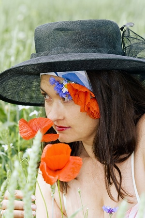 Attractive woman in a hat on the summer wheat field among corn-flowers and poppy photo