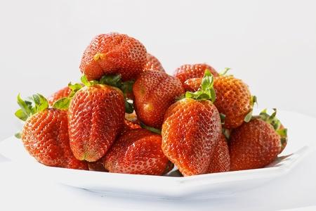 Fresh ripe strawberry on a white dish close-up photo