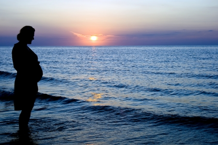 Pregnant lady on sunset background in Baltic sea photo