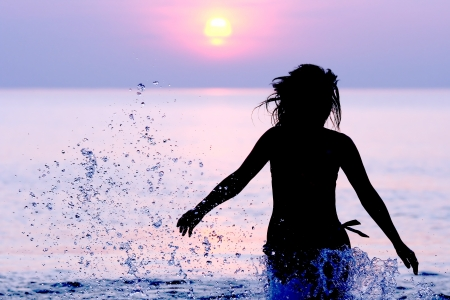 Woman in the sparks of water running on the Baltic sea at sunset photo