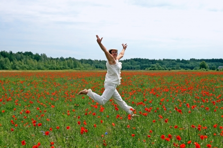 Happy female in a white dress jumps on the poppy field photo